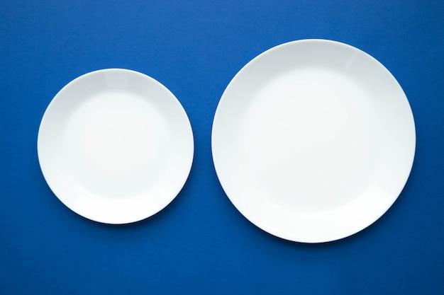 Due piatti bianchi vuoti su una tavola blu, una vista da sopra