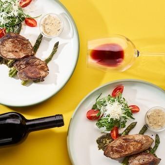 Due piatti con carne di maiale alla griglia con insalata di verdure fresche e vino rosso su una parete gialla. vista dall'alto