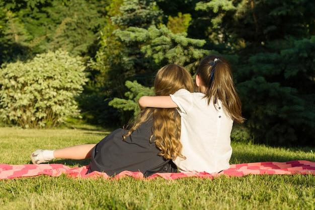 Due piccole amiche che abbracciano seduti su un prato nel parco.