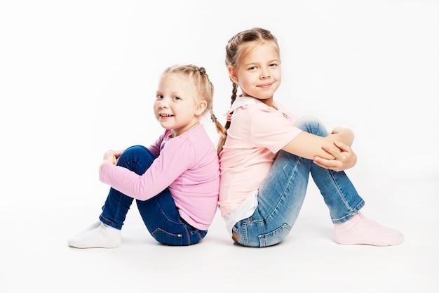 Due piccole amiche in jeans e maglioni rosa sono seduti e sorridenti. muro bianco.