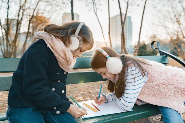 Due piccoli artisti graziosi che disegnano con le matite colorate