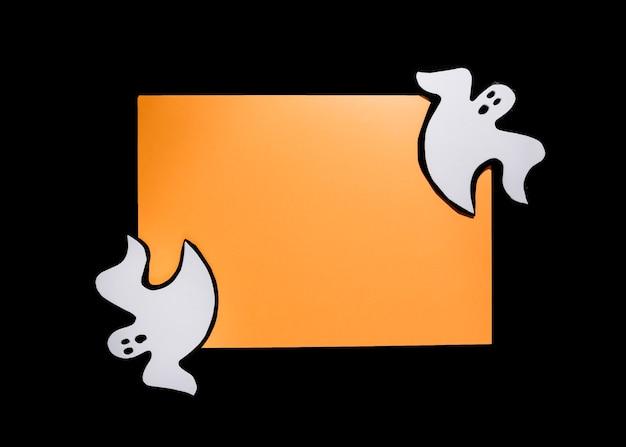 Due piccoli fantasmi appoggiati su angoli di carta