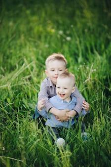 Due piccoli fratelli felici che indossano jeans e camicie a quadri a piedi nel parco
