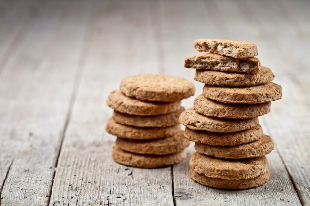Due pile di biscotti appena sfornati di avena sul tavolo in legno rustico