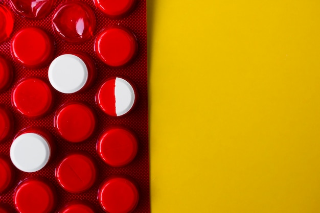 Due pillole rotonde bianche e mezzo sull'imballaggio rosso sul giallo