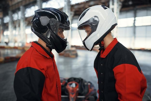 Due piloti di kart in caschi in piedi faccia a faccia