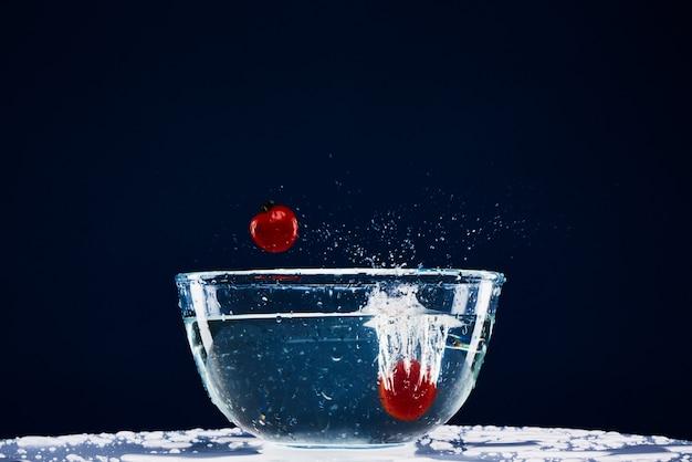 Due pomodori cadono giù nel cibo vegetariano di vetro.