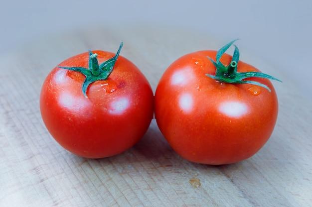 Due pomodori su uno sfondo di tavola di legno