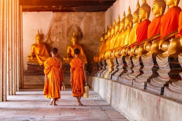Due principianti che camminano ritorno e parlando nel vecchio tempio al tramonto, provincia di ayutthaya, tailandia