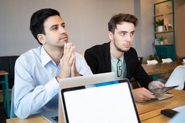 Due professionisti che ascoltano l'altoparlante della conferenza aziendale