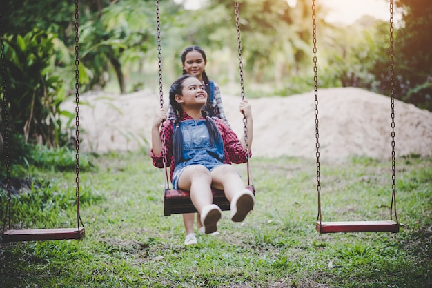 Due ragazza seduta su un'altalena insieme