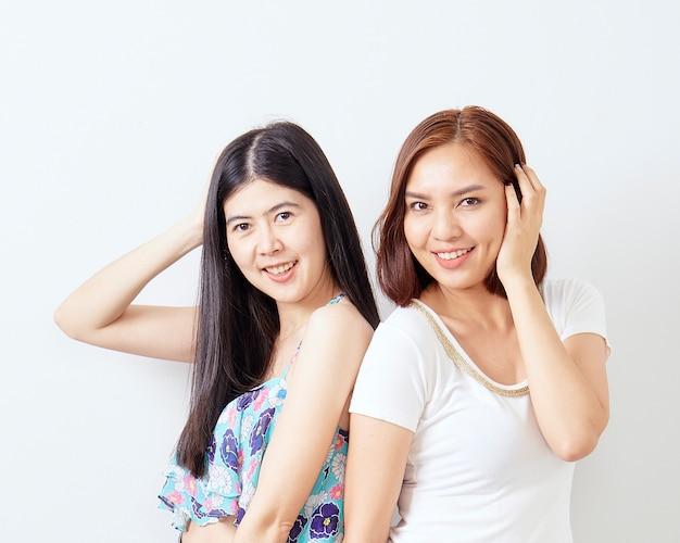 Due ragazze allegre che comperano sul bianco