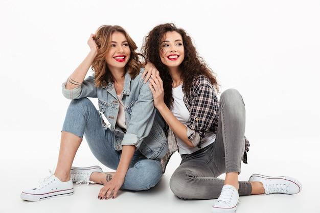 Due ragazze allegre che si siedono insieme sul pavimento e che distolgono lo sguardo sopra la parete bianca