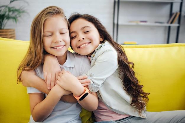 Due ragazze allegre che si siedono sul sofà e sull'abbraccio gialli. tengono gli occhi chiusi. bruna tenere la mano sulla spalla della sua amica. loro sorridono.
