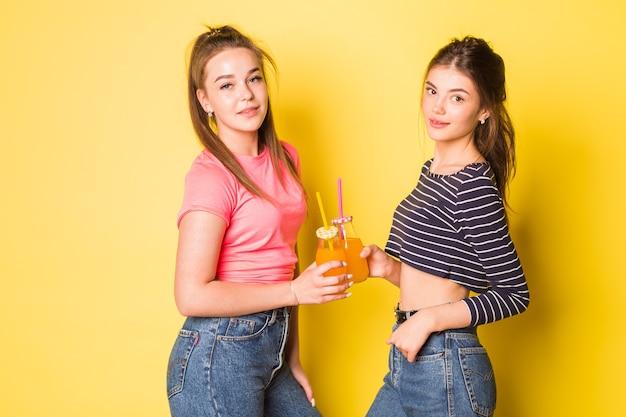 Due ragazze allegre giovani hipster di bellezza naturale che posano insieme su sfondo giallo