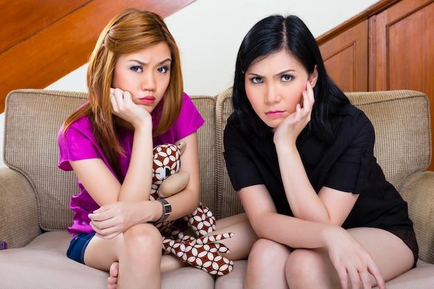 Due ragazze asiatiche a casa che sono annoiate o tristi
