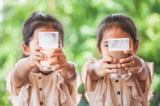 Due ragazze asiatiche sveglie del bambino che bevono un latte da vetro insieme