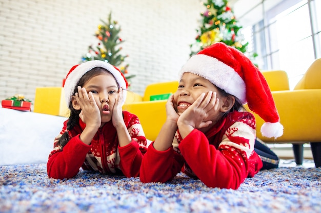 Due ragazze asiatiche sveglie del bambino che indicano sul pavimento e giocano insieme nella celebrazione di natale
