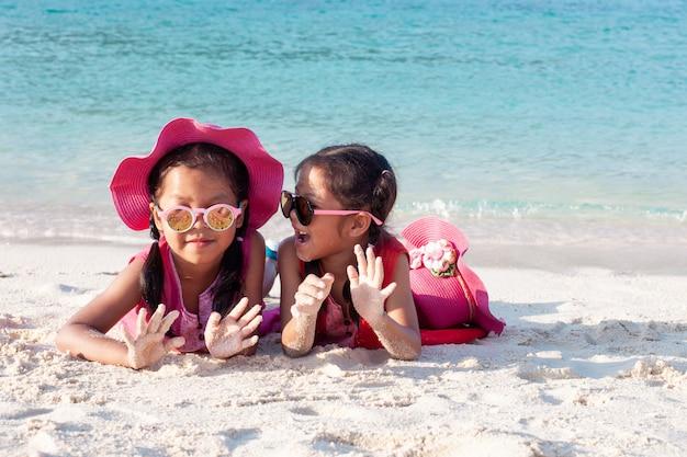 Due ragazze asiatiche sveglie del bambino che portano cappello e occhiali da sole rosa che giocano insieme con la sabbia sulla spiaggia