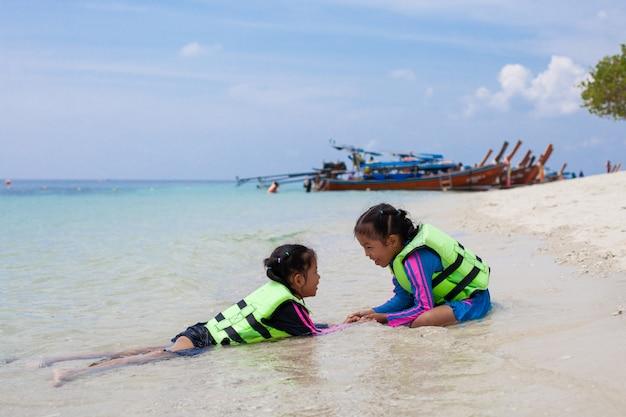 Due ragazze asiatiche sveglie del bambino che portano giubbotto salvagente che gioca acqua nel bello mare insieme al divertimento