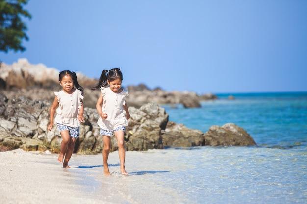 Due ragazze asiatiche sveglie del bambino che si divertono per giocare e funzionare insieme sulla spiaggia nelle vacanze estive