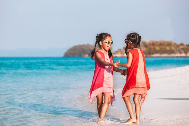 Due ragazze asiatiche sveglie del bambino che si tengono per mano e che giocano insieme sulla spiaggia