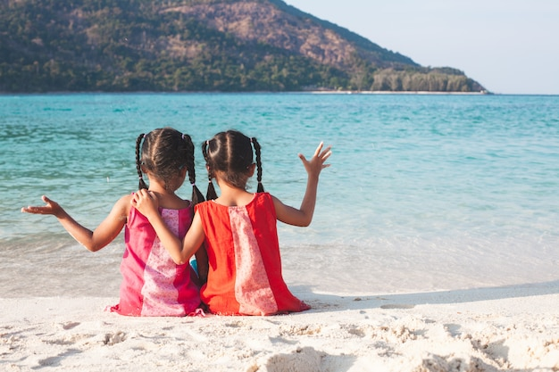 Due ragazze asiatiche sveglie del piccolo bambino che si siedono insieme e che giocano insieme sulla spiaggia