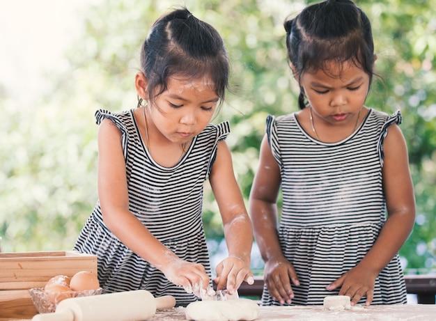 Due ragazze asiatiche sveglie del piccolo bambino preparano una pasta per i biscotti bollenti nella cucina