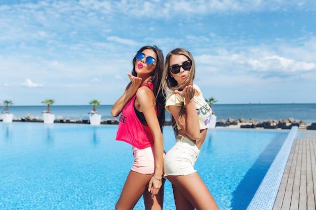 Due ragazze attraenti con i capelli lunghi in occhiali da sole sono in posa vicino alla piscina al sole. stanno in piedi schiena contro schiena.