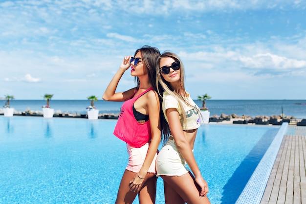 Due ragazze attraenti con i capelli lunghi sono in posa vicino alla piscina al sole. stanno in piedi schiena contro schiena.