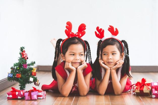 Due ragazze carina bambino asiatico con scatole regalo e albero di natale per festeggiare il natale