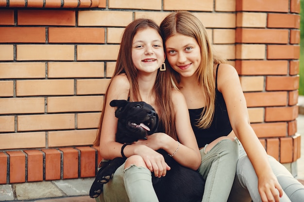 Due ragazze carine in un parco estivo con un cane