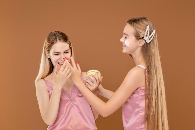 Due ragazze che applicano stupidamente faccia a faccia con la crema dell'acne
