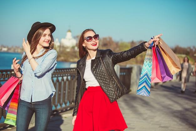 Due ragazze che camminano con i sacchetti della spesa sulle vie della città al giorno soleggiato