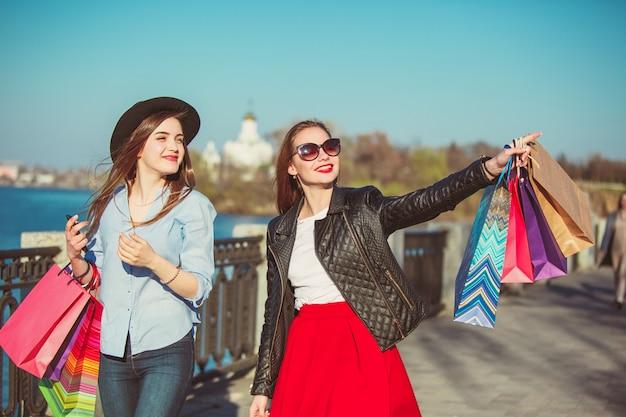 Due ragazze che camminano con lo shopping per le strade della città