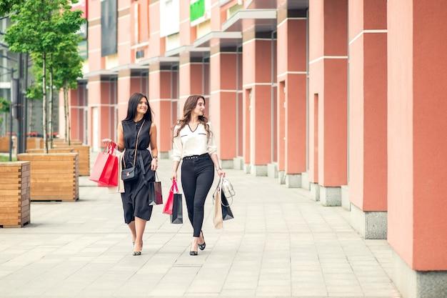 Due ragazze che camminano vicino al centro commerciale con le borse in mano.