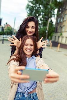 Due ragazze che fanno selfie divertenti per strada, divertendosi insieme