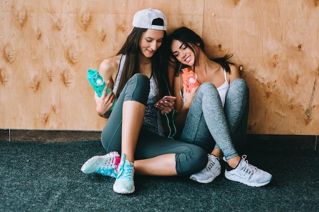 Due ragazze che hanno una pausa in palestra