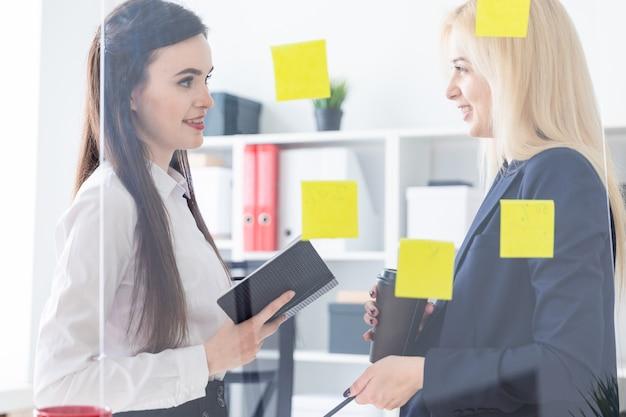 Due ragazze che parlano in ufficio. le ragazze dialogano vicino a una lavagna trasparente con adesivi.
