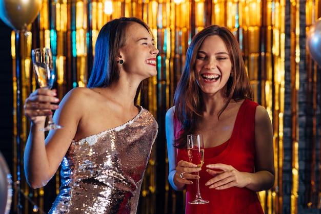 Due ragazze che ridono mentre si tengono bicchieri di champagne, amici per festeggiare capodanno, natale