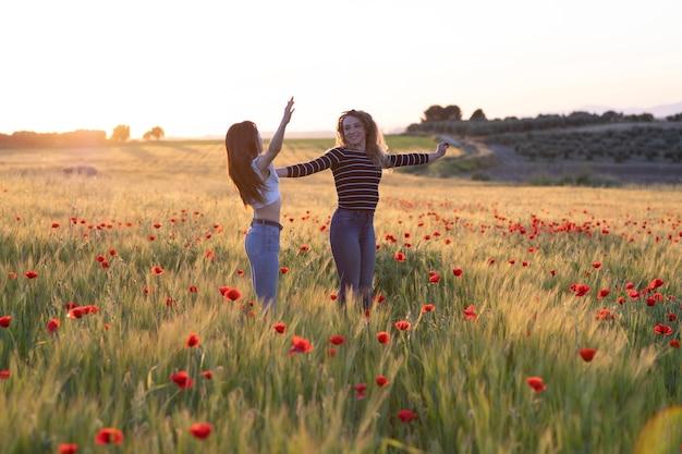 Due ragazze che saltano al tramonto nel campo del papavero