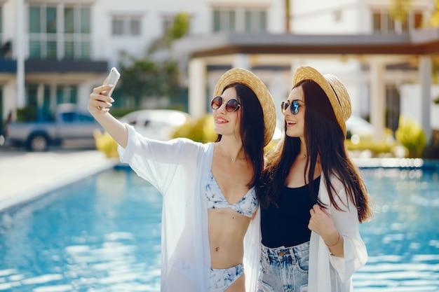 Due ragazze che si rilassano a bordo piscina e scattare foto sul proprio telefono