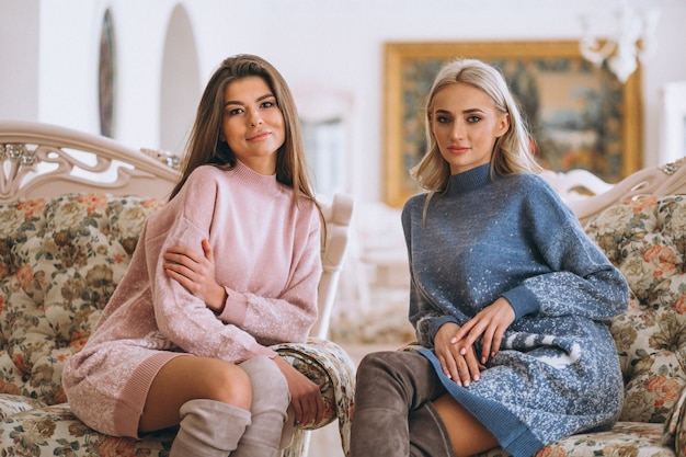 Due ragazze che si siedono sul divano e in chat
