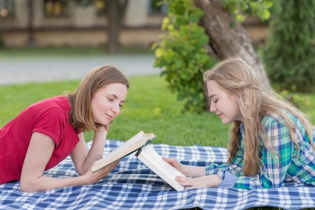 Due ragazze che studiano all'aperto sulla coperta da picnic