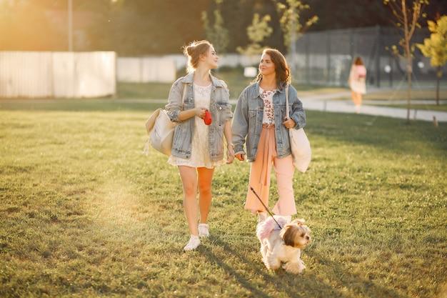 Due ragazze che wallking in un parco con un cagnolino