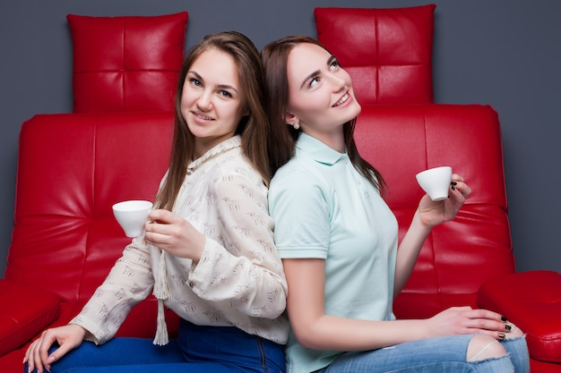 Due ragazze con tazze di caffè seduti insieme