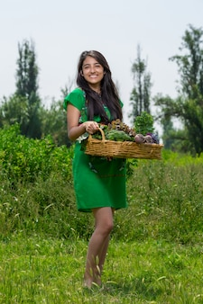 Due ragazze con un cesto di verdure in giardino