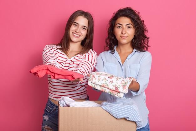 Due ragazze degli amici che tengono i vestiti nelle mani