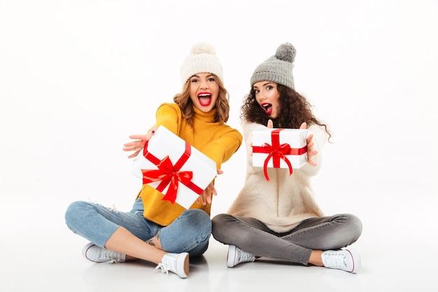 Due ragazze di grido felici in maglioni e cappelli che si siedono insieme con i regali sul pavimento sopra la parete bianca
