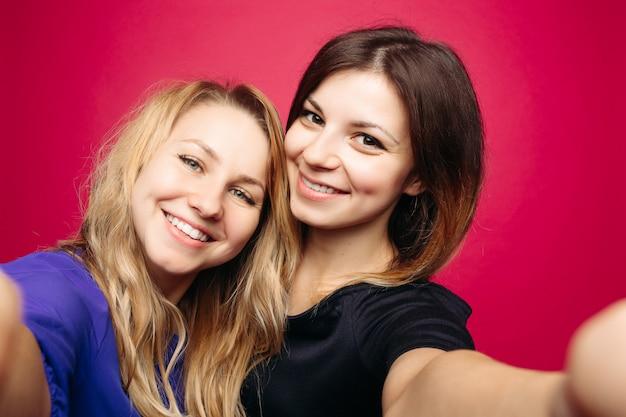 Due ragazze di positività che prendono autoritratto che sorride sul rosa